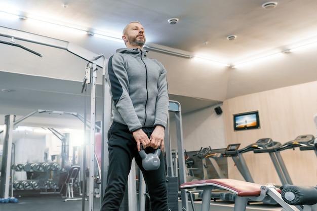 Brodaty mężczyzna robi ćwiczenia fizyczne na siłowni