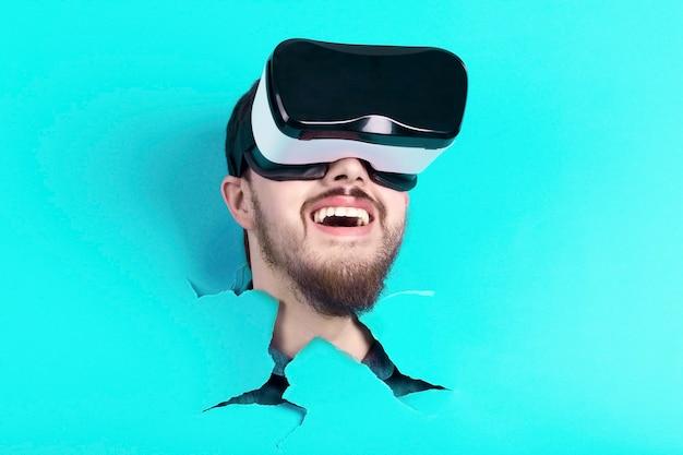 Brodaty mężczyzna robi dziurę w niebieskim papierze. zaskoczony mężczyzna w okularach wirtualnej rzeczywistości. urządzenie vr.