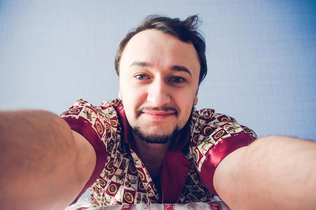 Brodaty mężczyzna robi selfie rano