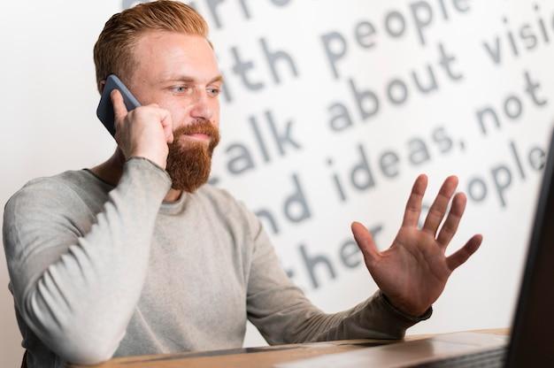 Brodaty mężczyzna rozmawia przez telefon