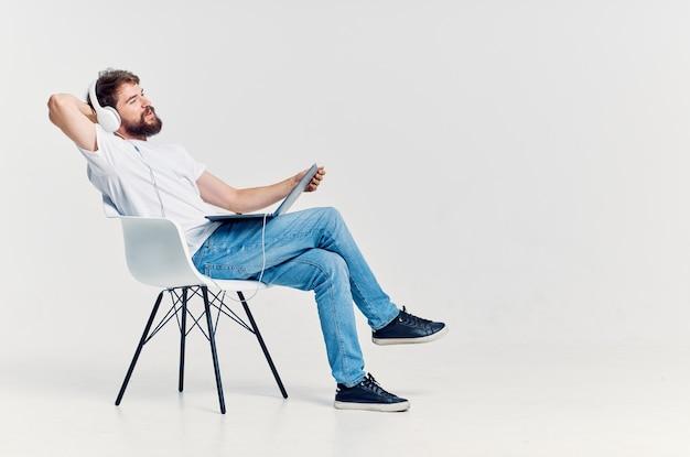 Brodaty mężczyzna siedzący na krześle z laptopem w słuchawkach rozrywka