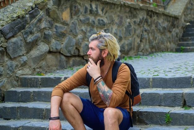 Brodaty mężczyzna siedzący na schodach stylowy facet siedzący na schodach przystojny mężczyzna na zewnątrz męski fryzjer