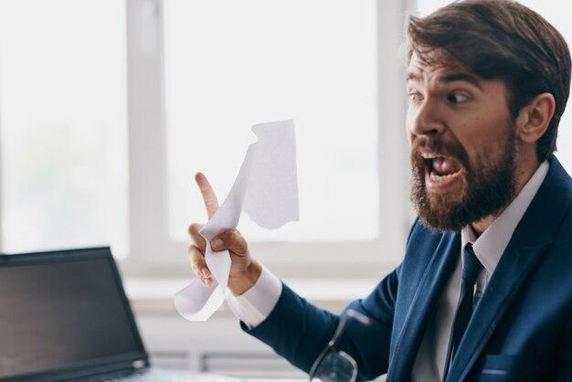 Brodaty mężczyzna siedzący przy biurku przed laptopem zestresowany gniewem