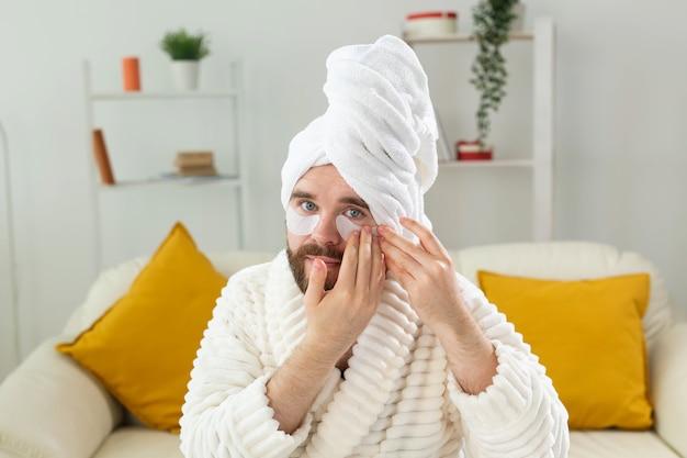 Brodaty mężczyzna siedzący z przepaskami na oczy na zmarszczkach na twarzy i domowej pielęgnacji twarzy dla mężczyzn