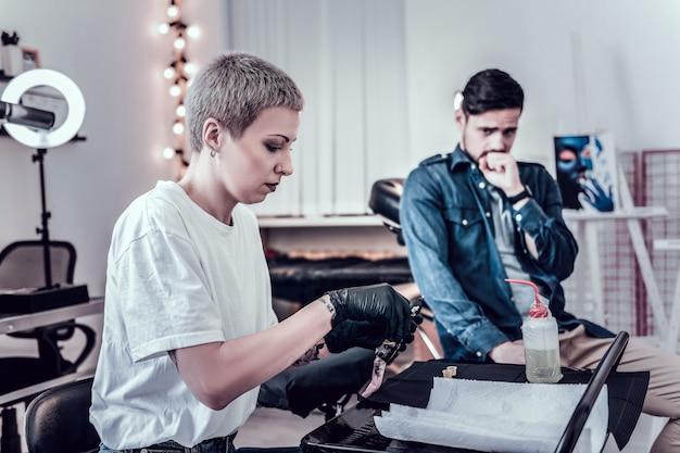 Brodaty mężczyzna siedzi. ciemnowłosy przystojny facet boi się robienia tatuaży, patrząc na ustawienie urządzenia