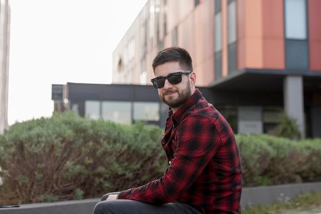 Brodaty mężczyzna siedzi i patrzeje kamerę z okularami przeciwsłonecznymi