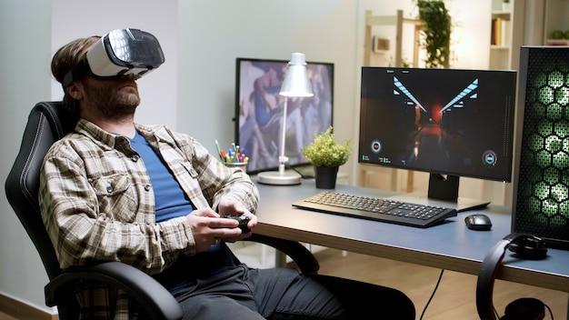 Brodaty mężczyzna siedzi na fotelu do gier, grając w gry za pomocą zestawu słuchawkowego vr. kobieta w tle.