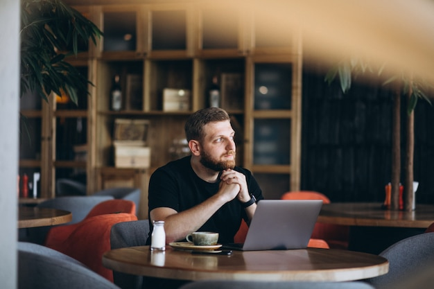 Brodaty mężczyzna siedzi w kawiarni picia kawy i pracy na komputerze