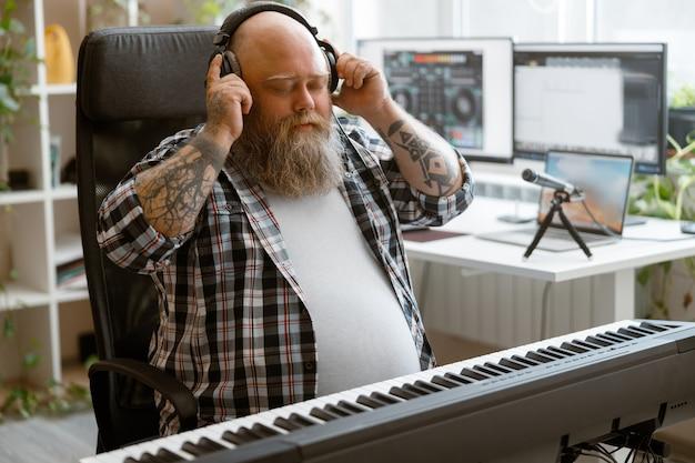 Brodaty mężczyzna słucha muzyki w słuchawkach siedzących przy syntezatorze dźwięku w domowym studio