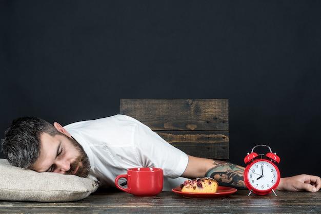 Brodaty mężczyzna śpi przy stole na poduszce z budzikiem i filiżanką kawy w kuchni wyczerpany mężczyzna