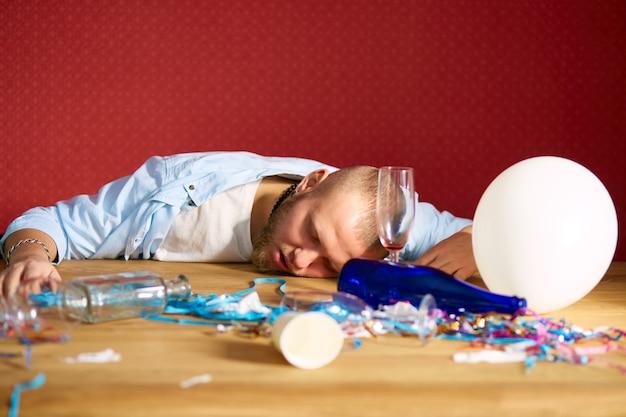 Brodaty mężczyzna śpi przy stole w brudnym pokoju po wieczorze kawalerskim, zmęczony mężczyzna po imprezie w domu