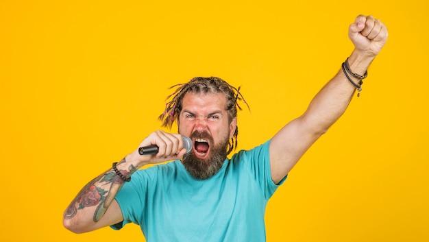 Brodaty mężczyzna śpiewa karaoke. nagrania studyjne. atrakcyjna piosenkarka śpiewa z mikrofonem.