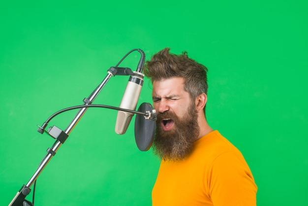 Brodaty mężczyzna śpiewa w mikrofonie mężczyzna karaoke śpiewa z mikrofonem śpiewa w mikrofonie studyjnym