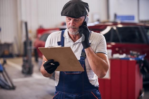 Brodaty mężczyzna sprawdza notatki podczas rozmowy telefonicznej na stacji obsługi samochodów