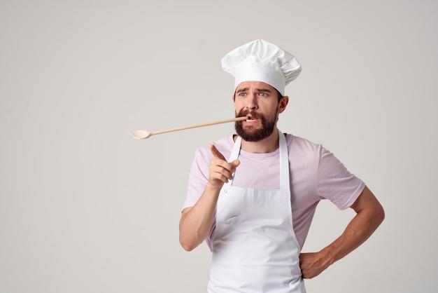 Brodaty mężczyzna szef kuchni w jednolitej łyżce w zęby pracujący w restauracji