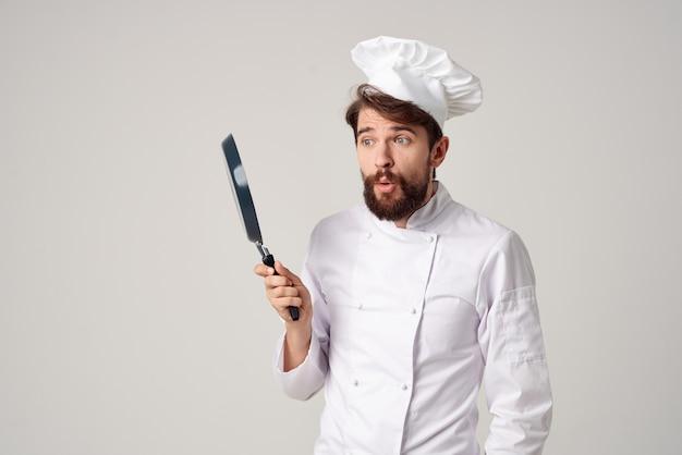 Brodaty mężczyzna szef kuchni z patelnią w dłoni jasnym tle