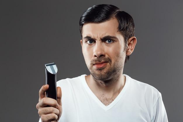Brodaty mężczyzna trzyma brzytwę, potrzebuje włosia do golenia