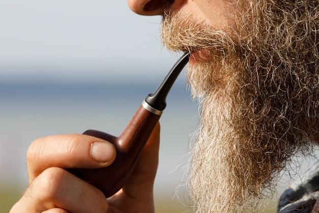 Brodaty mężczyzna trzyma fajkę w ustach, widok z boku