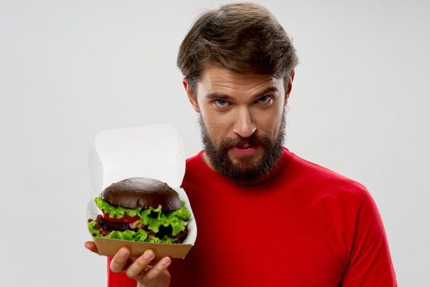 Brodaty mężczyzna trzyma hamburgera w pudełku