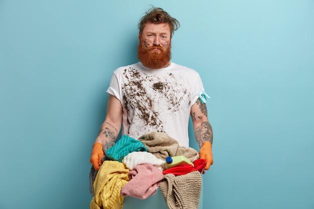 Brodaty mężczyzna trzyma kosz na bieliznę, przytłoczony obowiązkami domowymi