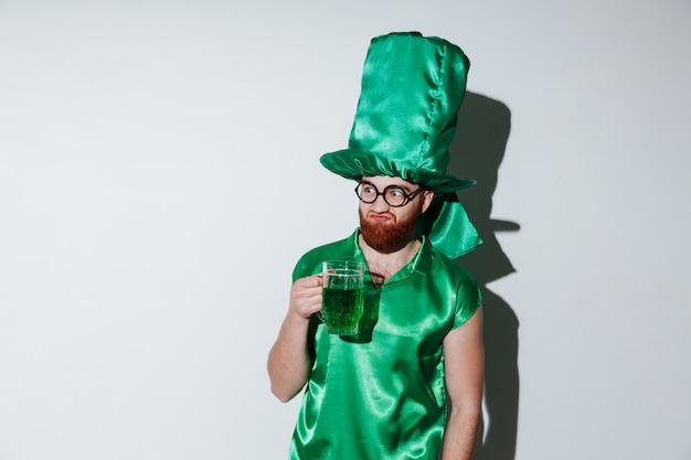 Brodaty mężczyzna trzyma kubek w zielonym stroju i okularach
