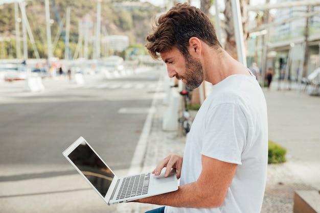 Brodaty mężczyzna trzyma laptopa odkryty