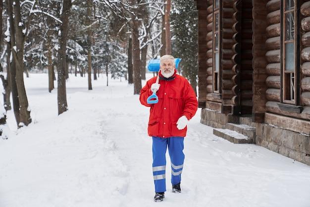 Brodaty mężczyzna trzyma łopatę i idzie naprzód w parku