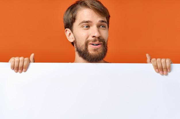 Brodaty mężczyzna trzyma makieta plakat zniżki pomarańczowe tło