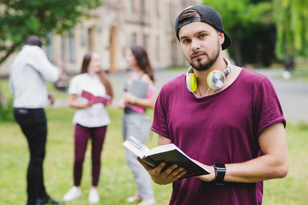 Brodaty mężczyzna trzyma podręcznik stały