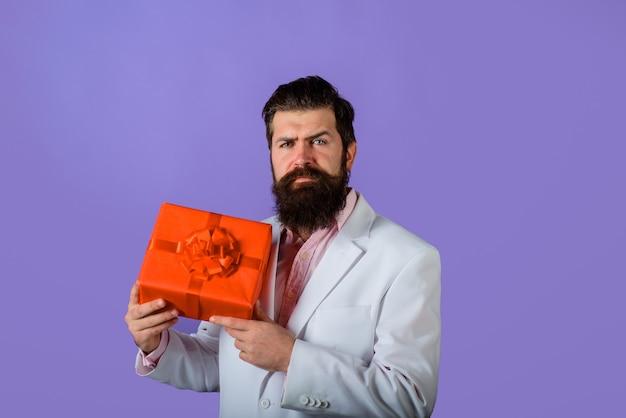Brodaty mężczyzna trzyma pudełko na prezent atrakcyjny mężczyzna z prezentem biznesmen trzyma pudełko na prezent walentynki