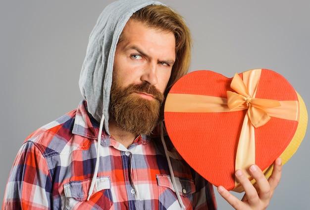 Brodaty mężczyzna trzyma pudełko na prezent w kształcie serca. podaruj z miłością. kup prezenty i prezenty. czas na prezenty.