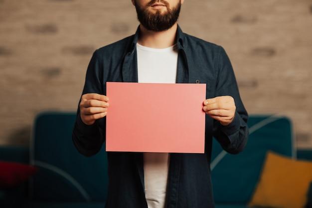 Brodaty mężczyzna trzyma różowy papier z miejsca na kopię.