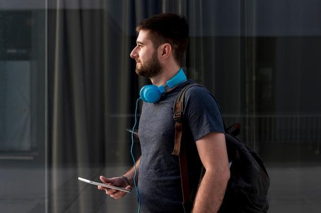 Brodaty mężczyzna trzyma smartphone z hełmofonami