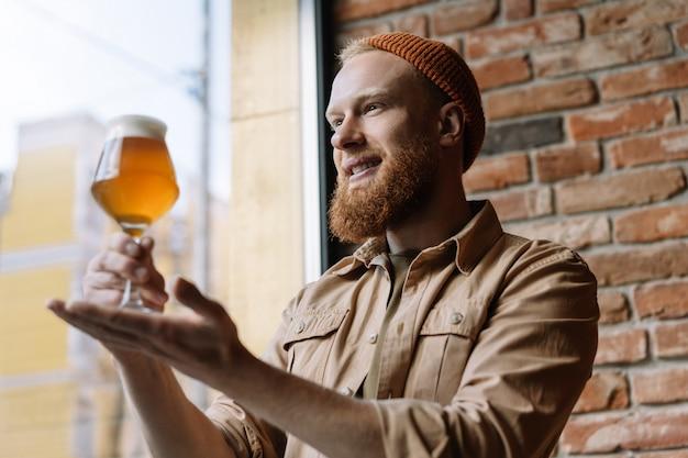 Brodaty mężczyzna trzyma szkło z piwem