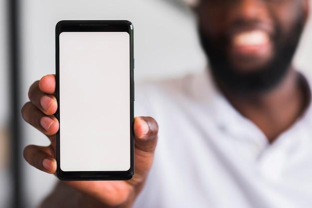 Brodaty mężczyzna trzyma telefon komórkowy