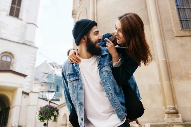 Brodaty mężczyzna trzyma uśmiechniętą damę na jego plecy stoi przed starą katedrą