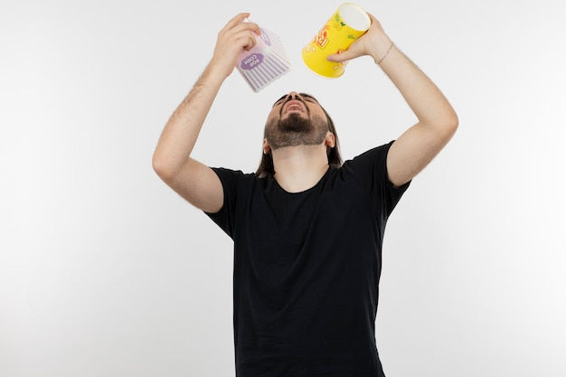 Brodaty mężczyzna trzyma wiadra popcornu.