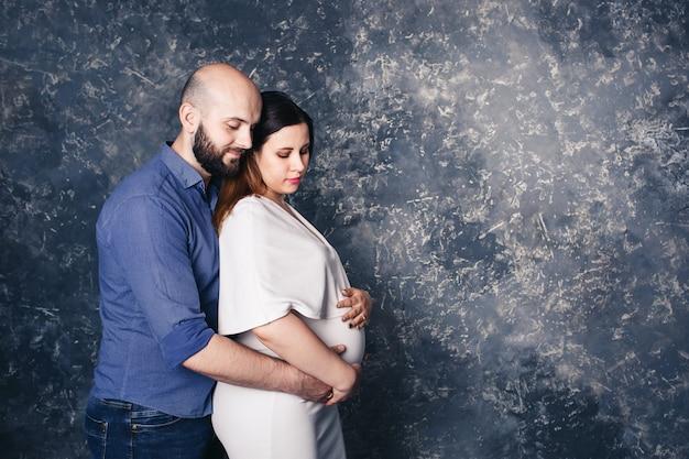 Brodaty mężczyzna trzymając ciężarną żonę przez brzuch na abstrakcyjnej powierzchni.