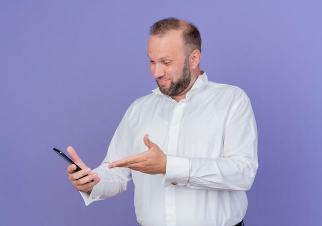 Brodaty mężczyzna ubrany w białą koszulę, patrząc na ekran swojego smartfona, prezentując z uśmiechem ramię stojąc nad niebieską ścianą