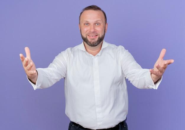Brodaty mężczyzna ubrany w białą koszulę, patrząc uśmiechnięty, przyjazny, szeroko otwierający się dłonie, witający stojący nad niebieską ścianą