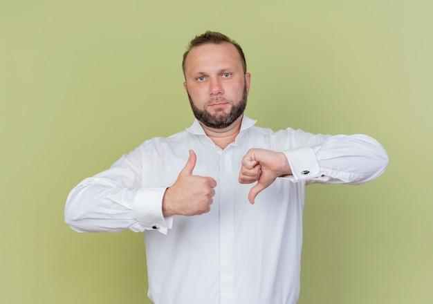Brodaty mężczyzna ubrany w białą koszulę pokazując kciuki w górę iw dół stojąc nad jasną ścianą