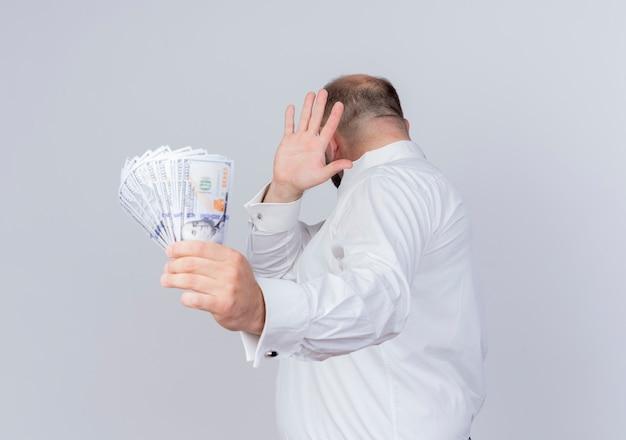 Brodaty mężczyzna ubrany w białą koszulę, trzymając gotówkę, czyniąc gest obrony ręką przed pieniędzmi stojąc na białej ścianie