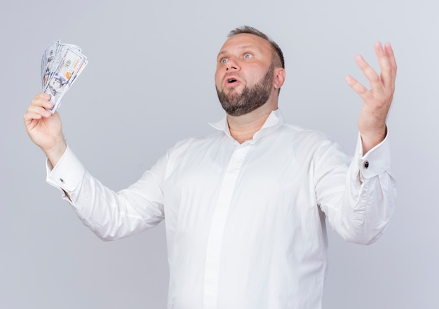 Brodaty mężczyzna ubrany w białą koszulę, trzymając gotówkę, patrząc na bok podnosząc rękę, zaskoczony i bardzo zaniepokojony stojąc nad białą ścianą
