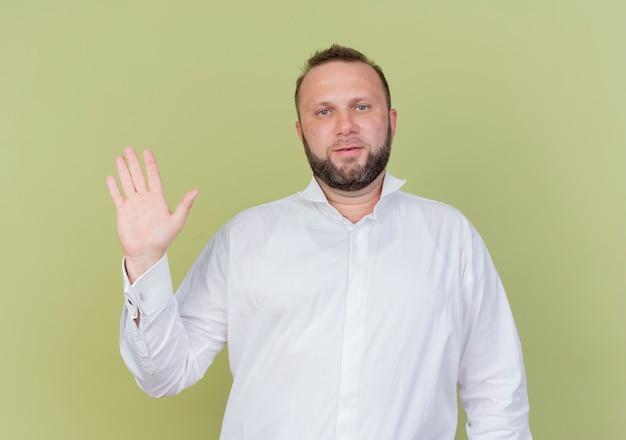 Brodaty mężczyzna ubrany w białą koszulę uśmiechnięty macha ręką stojącą nad jasną ścianą