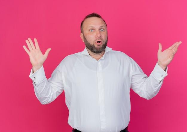 Brodaty mężczyzna ubrany w białą koszulę zdezorientowany i niepewny podnoszący ręce stojący nad różową ścianą