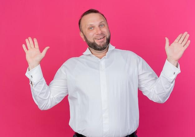 Brodaty mężczyzna ubrany w białą koszulę, zdezorientowany, uśmiechnięty, podnosząc ręce, stojąc na różowej ścianie