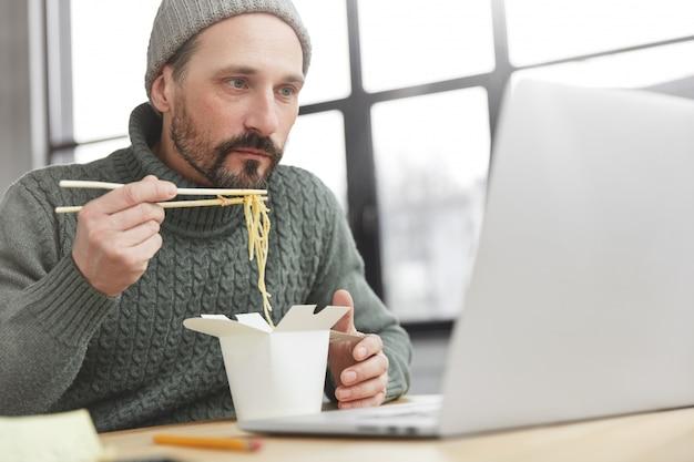 Brodaty mężczyzna ubrany w ciepły sweter z dzianiny i kapelusz po obiedzie