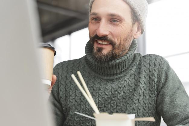 Brodaty mężczyzna ubrany w ciepły sweter z dzianiny i kapelusz