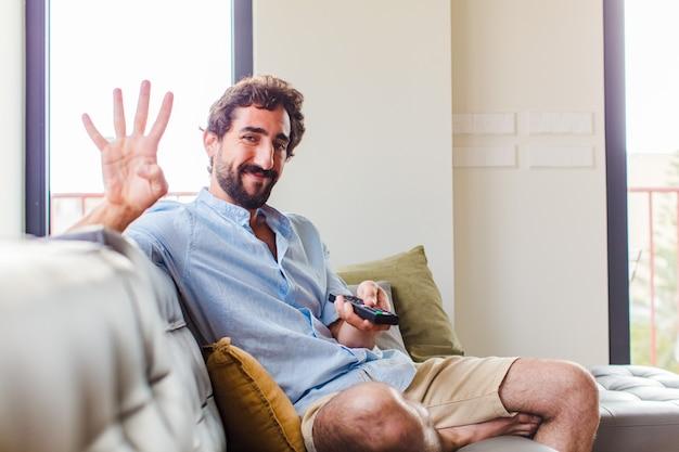 Brodaty mężczyzna uśmiechnięty i wyglądający przyjaźnie, pokazujący numer cztery lub czwarty z ręką do przodu, odliczający