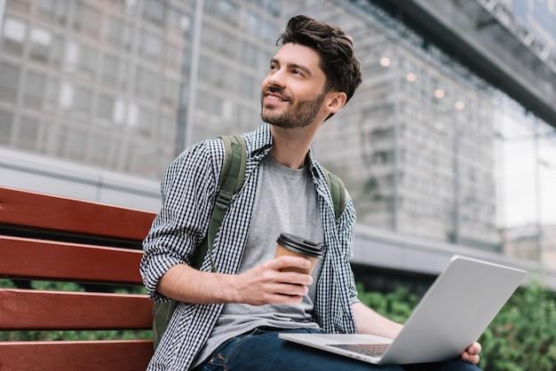 Brodaty mężczyzna używa laptop, planuje projekt, pije kawę. modnisia uczeń studiuje outdoors